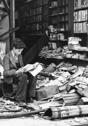 Photograph of a boy reading a book amongst rubble during the London blitz