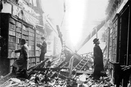 Photograph of two men looking at books in the rubble of a library bombed during the London blitz
