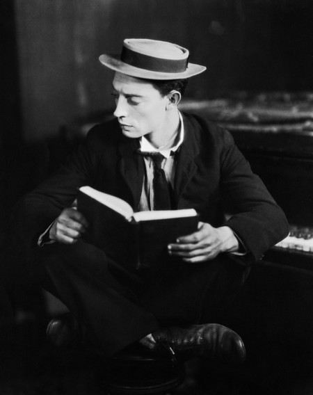 Photograph of the silent film actor Buster Keaton reading a book