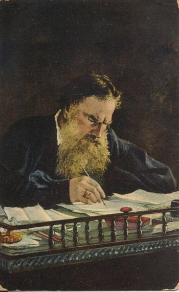 Portrait of a bearded man writing at a desk full of papers
