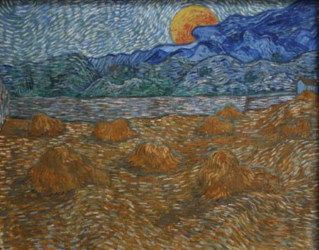 The moon rising from behind a mountain over a wheat field