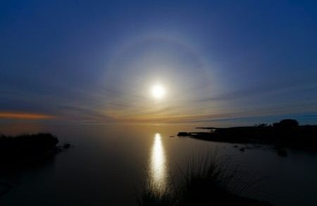 Photograph of the moon over the ocean surrounded by a halo of light