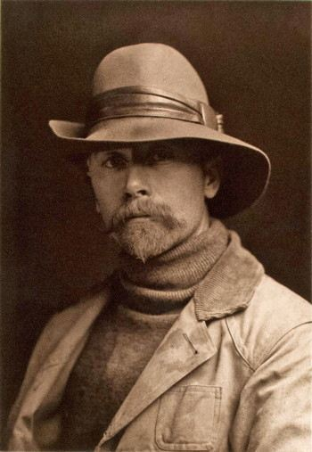 Photograph of a man with a goatee wearing a fedora hat, turtleneck, and an outdoor jacket