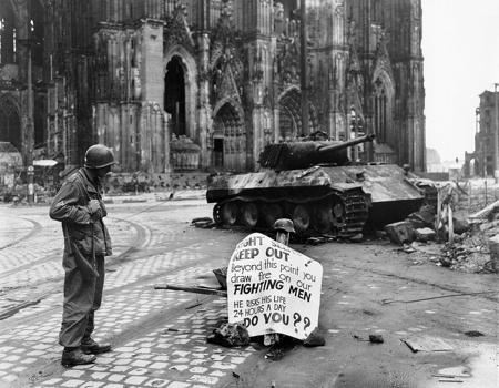 Phoograph of a G. I. eading a warning sign in front of the Cathedral at Köln