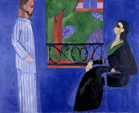 A man and a woman (man standing, woman seated) having a conversation