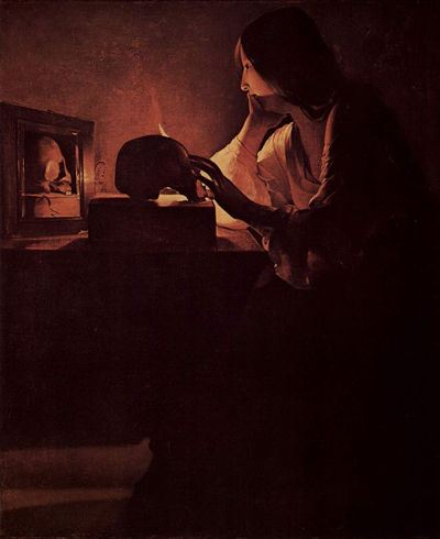 Woman sitting in front of a mirror with two lit candles